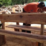 Andrea a high school student puts finishing touches on his Casuarinas bench for Earth Day